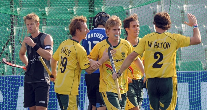 New Zealand hockey captain Dean Couzins (L) watches as South African hockey player Taine Paton (3rd R) celebrates a goal against New Zealand with teammates during their World Cup 2010 classification match for 9th and 10th place at the Major Dhyan Chand Stadium in New Delhi on March 12, 2010. New Zealand and South Africa tied at 4-4 till extra time. (AFP Photo)