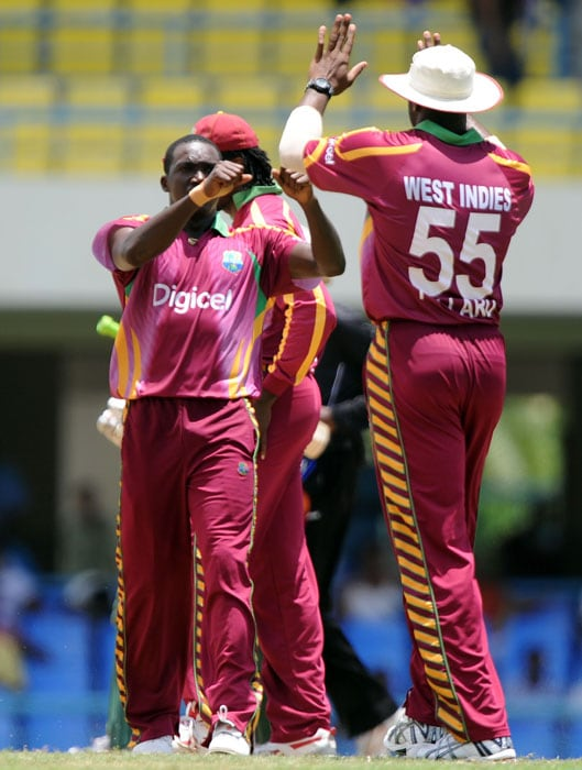 West Indies cricketer Jerome Taylor celebrates with teammates after dismissing South African batsman Hashim Amla. Amla scored 92-runs before being dismissed. (AFP PHOTO)