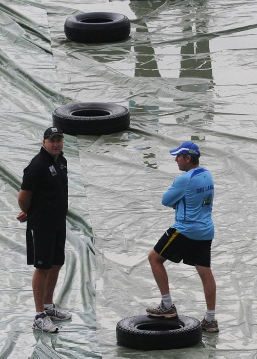 New Zealand cricket coach Mark Greatbatch talks with Sri Lankan coach coach Trevor Bayliss during a rain break during the fourth ODI between Sri Lanka and New Zealand at the Rangiri Dambulla International stadium in Dambulla. (AFP Photo)