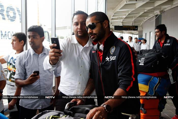 Shikhar Dhawan waits file a fan takes a picture with him.