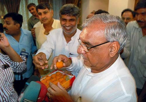 Haryana Chief Minister Bhupinder Singh Hooda distributing sweets after watching through TV the winning match of boxer Vijender at Beijing Olympics, in Chadigarh on Wednesday. (PTI)
