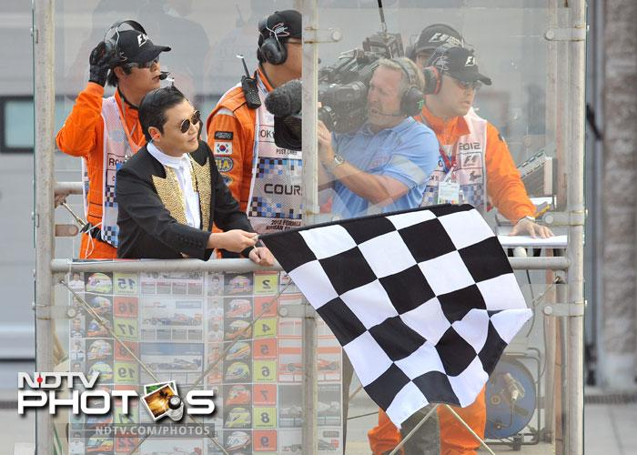 Worldwide sensation Psy brought 'Gangnam Style' to the Korean Grand Prix by first showing Red Bull's drivers Sebastian Vettel and Mark Webber how to dance to his crazy number and then waving the chequered flag as Vettel won the race. (All AFP Photos)