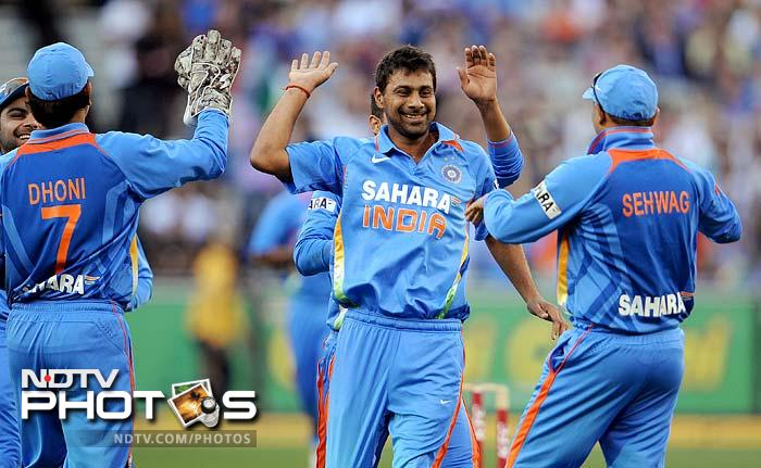 Indian bowler Praveen Kumar (C) celebrates with teammates after dismissing Australian batsman Shaun Marsh in the their international T20 cricket match at the MCG.