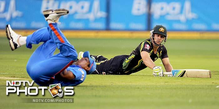 Australian batsman Matthew Wade (R) slides into the crease as Indian fieldsman Rahul Sharma (L) attempts to field in the their international T20 cricket match at the MCG.