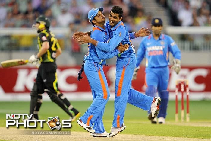 Indian bowler Ravindra Jadeja (2/R) is congratulated by teammate Suresh Raina (2/L) after dismissing Australian batsman David Hussey (L) in the international T20 cricket match at the MCG.