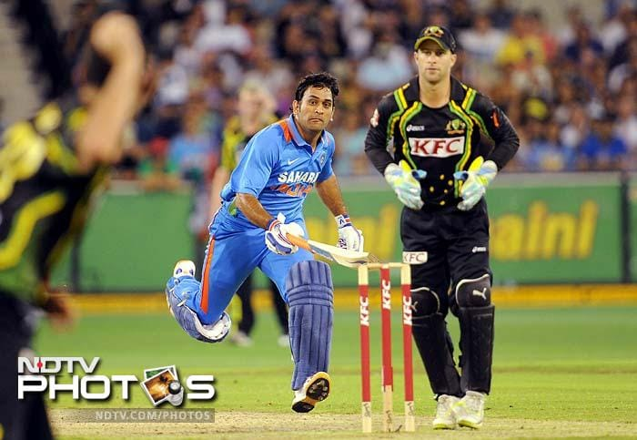 Indian batsmen MS Dhoni (C) takes a quick single as Australian wicketkeeper Matthew Wade (R) looks on as India defeat Australia in the international T20 cricket match at the MCG.