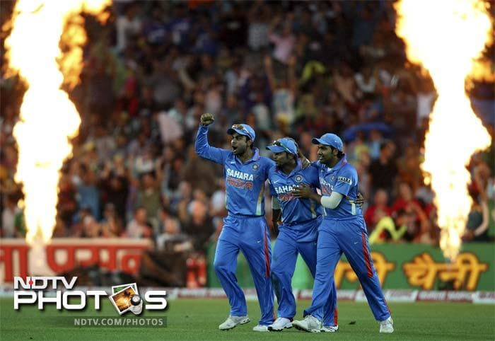 Indian players, from left, Virat Kohli, Suresh Kumar and Rohit Sharma, celebrate taking the wicket of Australia's David Warner during their Twenty 20 International match in Sydney.
