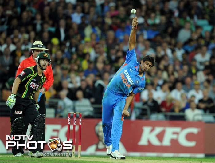 Rahul Sharma (R) from India bowls against Australia during the Twenty20 cricket match in Sydney.