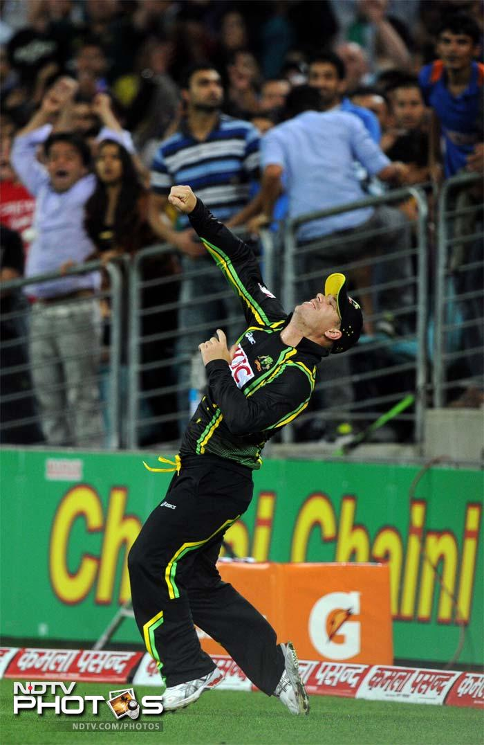 Australia's David Warner celebrates after taking a catch to dismiss India's Virat Kohli during the Twenty20 cricket match in Sydney.