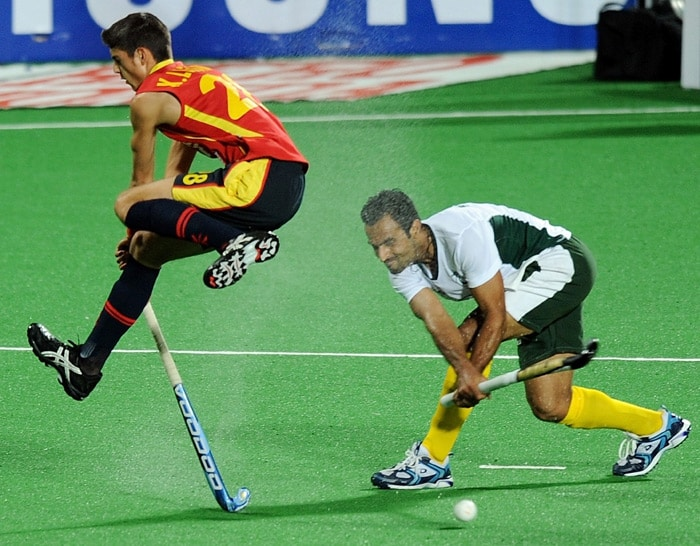 Spanish hockey player Xavi Lleonart vies for the ball with Pakistani hockey player Sohail Abbas during their World Cup 2010 match at the Major Dhyan Chand Stadium in New Delhi. (AFP Photo)