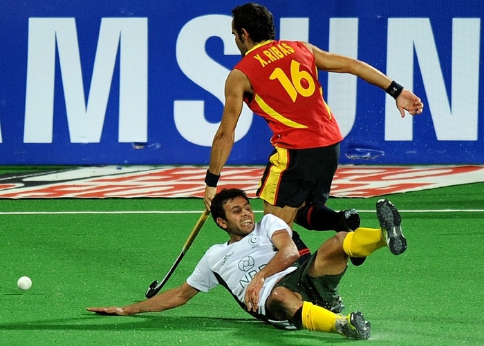 Spanish hockey player Xavier Ribas vies for the ball with Pakistani hockey player Rehan Butt during their World Cup 2010 match at the Major Dhyan Chand Stadium in New Delhi. (AFP Photo)