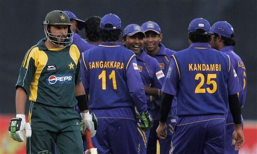 Shahid Afridi, left, walks back to pavilion as Sri Lankan players celebrate his dismissal during their third one-day international cricket match at Gaddafi Stadium in Lahore on Saturday, January 24, 2009. (AP Photo)