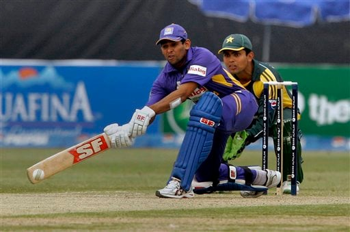 Sri Lankan batsman Tillakaratne Dilshan, front, plays a shot as Pakistani wicketkeeper Kamran Akmal, back, looks on during their third one-day international cricket match at Gaddafi Stadium in Lahore on Saturday, January 24, 2009. (AP Photo)