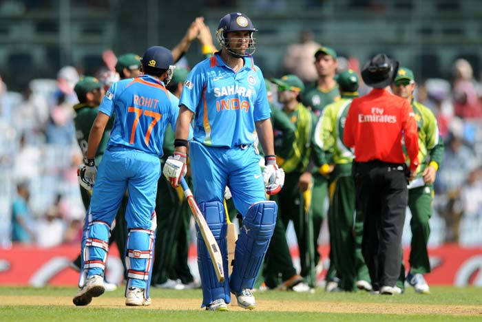 Yuvraj Singh seen here, makes his way back as Pakistan celebrate behind him. Five of six wickets that fell in the day left the wickets in tatters. (Image courtesy: BCCI)