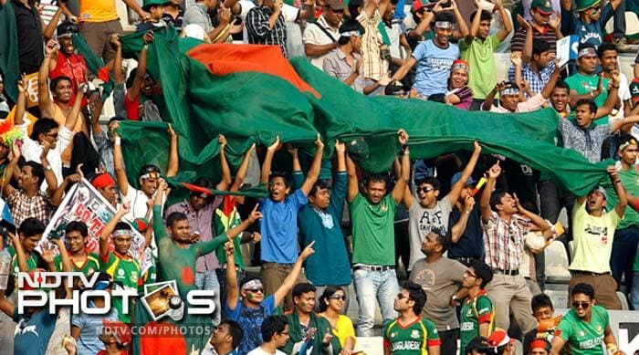 Bangladesh supporters hold their national flag as they cheer for their team during the Asia Cup final cricket match between Bangladesh and Pakistan in Dhaka.