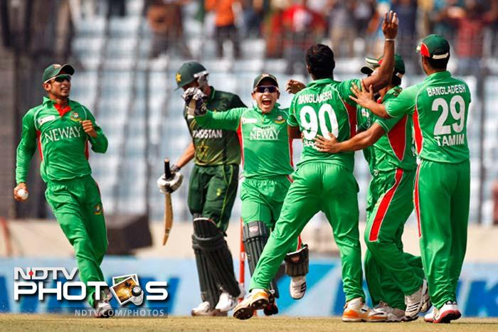 Bangladesh's wicketkeeper Mushfiqur Rahim, third left, and Nasir Hossain, left, celebrates with teammates the dismissal of Pakistan's Younus Khan during their Asia Cup final cricket match in Dhaka.