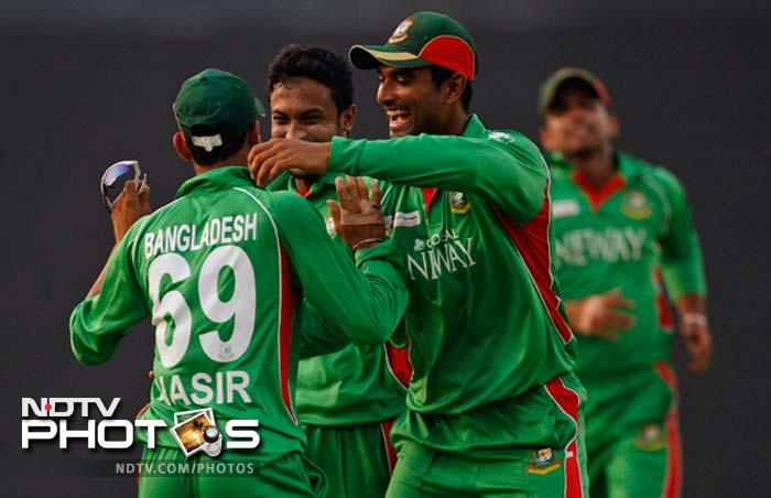 Bangladesh's Mahmudullah, second right, and Shakib Al Hasan, second left, congratulates teammate Nasir Hossain, back to camera, for the dismissal of Pakistan's Shahid Afridi during their Asia Cup cricket final match in Dhaka.