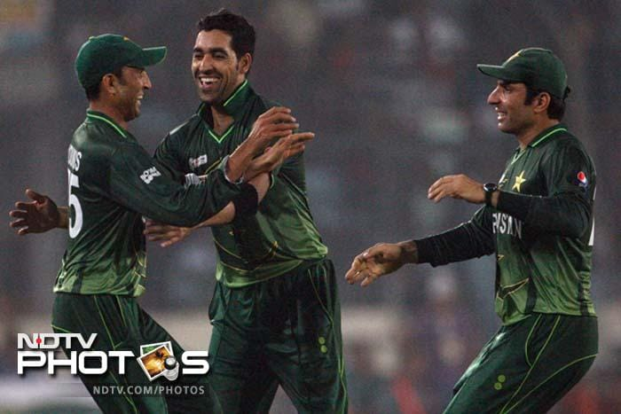 Pakistan's Umal Gul, center, and Misbah Ul Haq, right, celebrate with Younus Khan the dismissal of Bangladesh's Nazimuddin during their Asia Cup cricket match final in Dhaka.