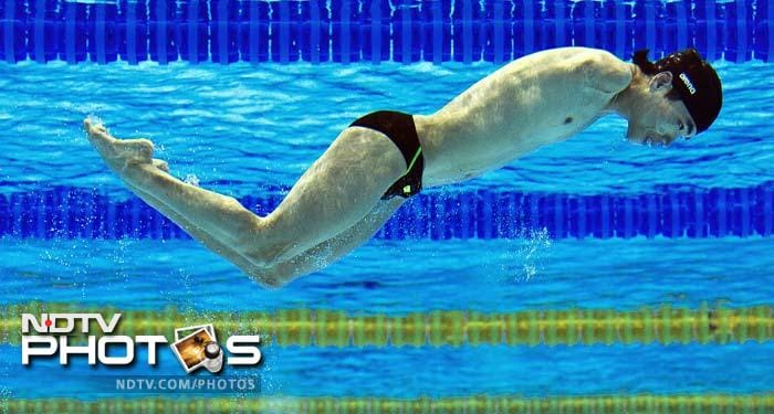 A Chinese swimmer is seen through an underwater window during a practice session.