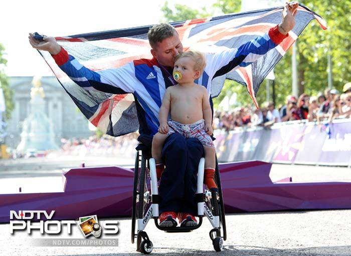 Great Britain's David Weir holds a Union Flag as he celebrates with his son Mason after collecting his gold medal for winning the men's Marathon T54 race.