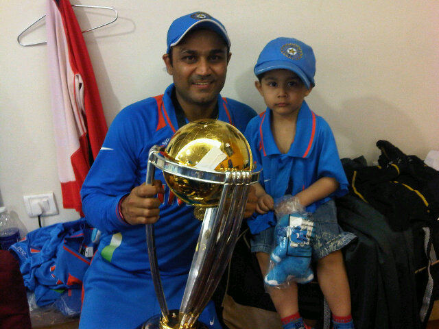 Smashing batsman Virender Sehwag and his little one with the World Cup trophy.