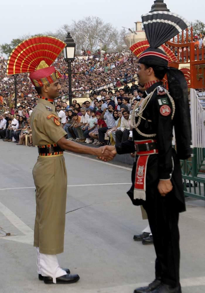 An Indian Border Security Force soldier and Pakistani Ranger, in black, shake hands during the daily retreat ceremony on the Pakistan-India border at Wagah near Lahore, Pakistan. (AP Photo)