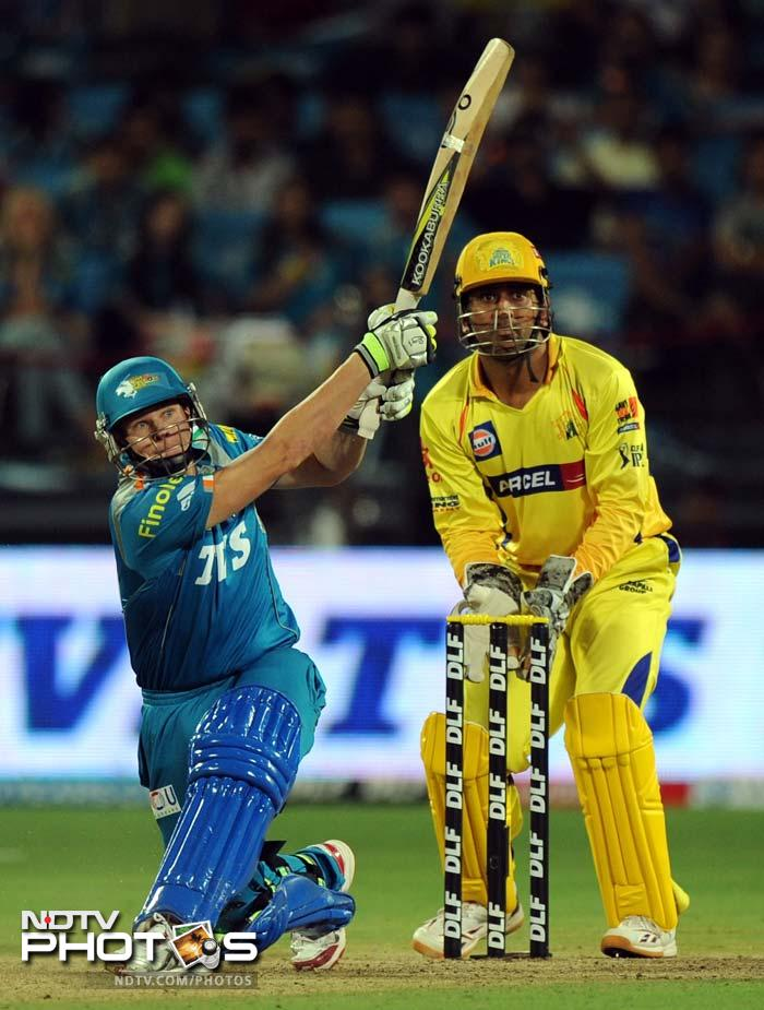 Pune Warriors India batsman Steven Smith (L) is watched by Chennai Super Kings captain Mahendra Singh Dhoni as he plays a shot during the IPL Twenty20 cricket match at the Subrata Roy Sahara Stadium in Pune. (AFP PHOTO/Indranil MUKHERJEE)