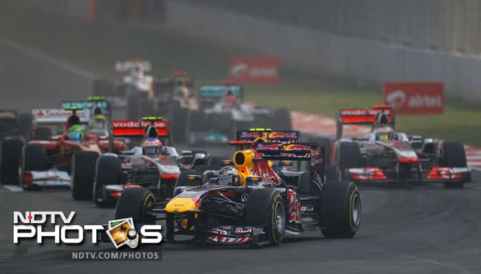 Red Bull driver Sebastian Vettel of Germany, center, leads the field after the start of the Indian Formula One Grand Prix at the Buddh International Circuit.