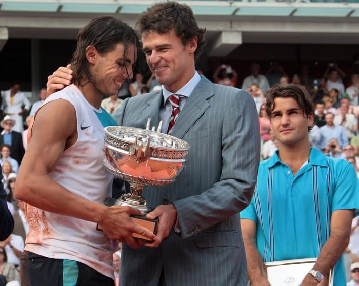 The story was same a year later as Nadal once again foiled Federer's attempt to complete a career Slam by beating the Swiss 6-3, 4-6, 6-2, 6-4 in the final of the French Open.<br><br> Here he is seen with Brazilian clay court specialist Gustavo Kuerten who was also a three-time champion at Roland Garros, handing over the trophy to him.