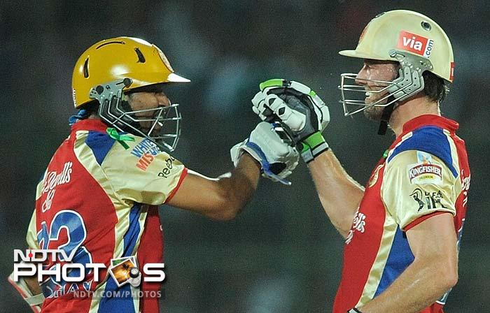 Dilshan is seen here with AB de Villers (right). The two smashed their way to the boundary repeatedly to take their team out of murky waters. (AFP PHOTO/ MANAN VATSYAYANA)