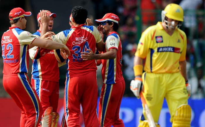 Royal Challengers Bangalore fielders congratulate bowler Zaheer Khan (C) for taking the wicket of Chennai Super Kings batsman Michael Hussey (R) during the IPL Twenty20 cricket match at the M.Chinnaswamy Stadium in Bangalore. (AFP PHOTO)