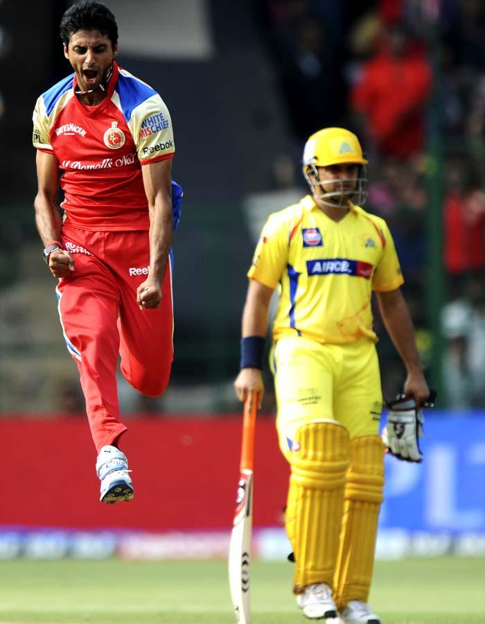 Royal Challengers Bangalore bowler Sreenath Aravind (R) is jubilant after taking the wicket of Chennai Super Kings batsman Murali Vijay as Chennai's Suresh Raina looks on during the IPL Twenty20 match at the M.Chinnaswamy Stadium in Bangalore. (AFP PHOTO)