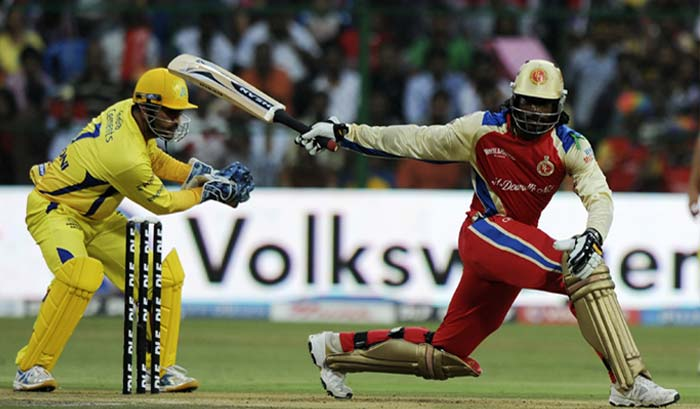 Royal Challengers Bangalore batsman Chris Gayle is watched by Chennai Super Kings captain Mahendra Singh Dhoni as he plays a shot during the IPL Twenty20 match at the M.Chinnaswamy Stadium in Bangalore. (AFP PHOTO)