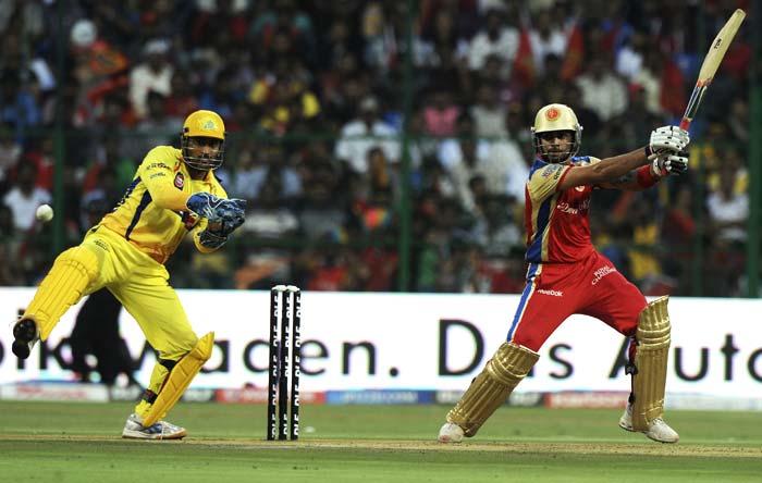 Royal Challengers Bangalore batsman Virat Kohli is watched by Chennai Super Kings captain Mahendra Singh Dhoni as he plays a shot during the IPL Twenty20 match at the M.Chinnaswamy Stadium in Bangalore. (AFP PHOTO)