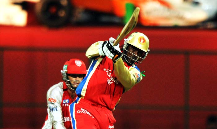 Royal Challengers Bangalore batsman Chris Gayle (R) is watched by Kings XI Punjab wicketkeeper Adam Gilchrist as he plays a shot during the IPL Twenty20 cricket match at the M.Chinnaswamy Stadium in Bangalore. (AFP PHOTO)