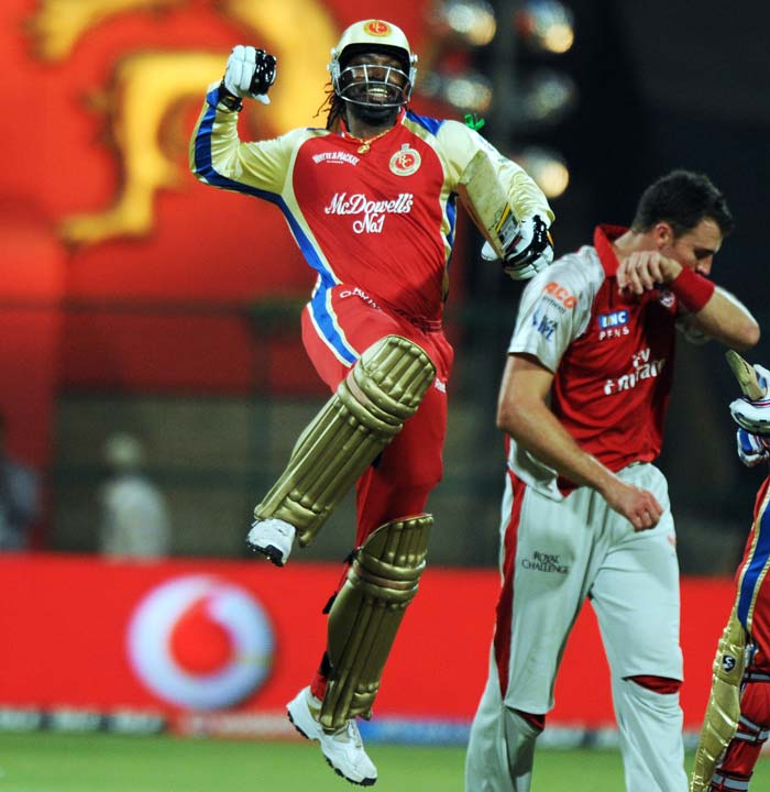 Royal Challengers Bangalore batsman Chris Gayle jumps in the air to celebrate his century as Kings XI Punjab bowler Ryan McLaren (R) stands by his side during the IPL Twenty20 cricket match at the M.Chinnaswamy Stadium in Bangalore. (AFP PHOTO)