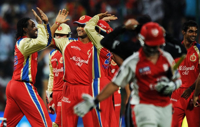 Royal Challengers Bangalore bowler Chris Gayle (L) celebrates with teammates after taking the wicket of Kings XI Punjab batsman Paul Valthaty during the IPL Twenty20 match at the M.Chinnaswamy Stadium in Bangalore. (AFP PHOTO)
