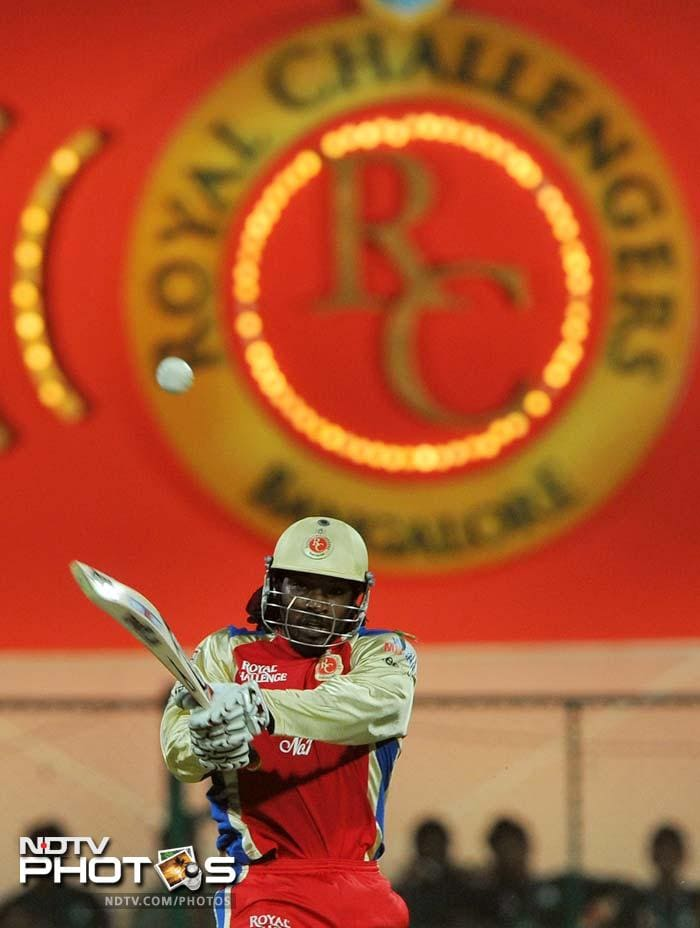 Chris Gayle had begun slowly finding the going tough against Praveen Kumar who gave away only 8 runs in his 4-over spell. (AFP PHOTO/Manjunath KIRAN)