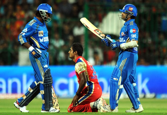 Mumbai Indians captain Sachin Tendulkar (R) talks with Ambati Rayudu as Royal Challengers Bangalore bowler Abhimanyu Mithun reacts after missing a ball during the IPL Twenty20 at the M.Chinnaswamy Stadium in Bangalore. Mumbai Indians won by 9 wickets. (AFP Photo)