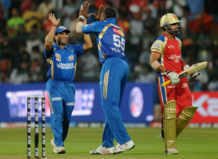 Mumbai Indians cricketers Sachin Tendulkar, left, and Kieron Pollard, center, celebrate the dismissal of Royal Challengers Bangalore's Virat Kohli, right, during an Indian Premier League (IPL) cricket match in Bangalore. (AP Photo)
