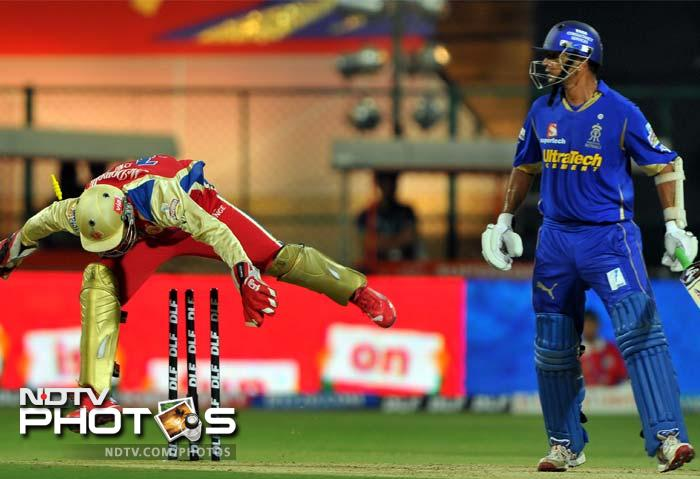 Royal Challengers Bangalore wicketkeeper AB de Villiers jumps over the wicket while stumping Rajasthan Royals captain Rahul Dravid (R) during the IPL Twenty20 cricket match at the M. Chinnaswamy Stadium in Bangalore. (AFP PHOTO/Manjunath KIRAN)