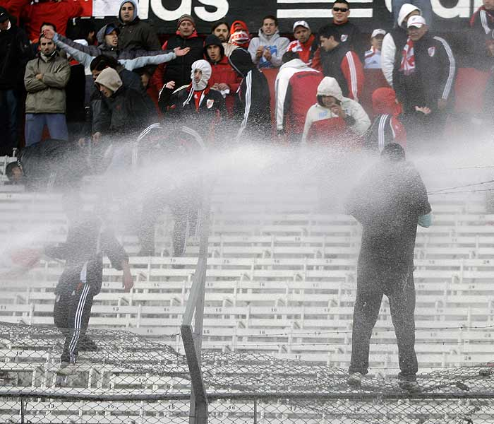 Violence broke a minute before the match was over. Angry fans pelted players with objects thrown from the stands, and police replied with high-powered fire hoses with some fans climbing restraining fences topped with razor wire. (AP Photo)