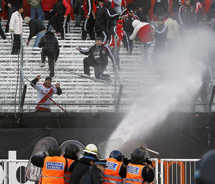 Police used water cannons outside the stadium immediately after the match, hoping to disperse fans quickly. Fans who poured out of the stadium faced police with batons and shields at every exit, while attack dogs were ready and helicopters hovered over the stadium. (AP Photo)