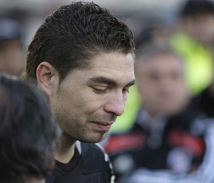 As fans were pounded with jets of water, River Plate's players huddled on the pitch, many in tears, including goalkeeper Juan Pablo Carrizo. (AP Photo)