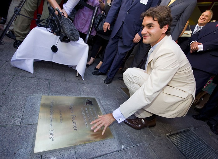 "World number one tennis player Roger Federer poses behind a plate bearing his name at the Basel ""Hall of Fame"" after an unveiling ceremony in Basel. Federer's Wimbledon triumph last July 6 has seen him regain the world number one spot from archrival Rafael Nadal. Federer won both the French Open and Wimbledon to chalk up a record 15 Grand Slam titles, one more than Pete Sampras. (AFP Photo)"