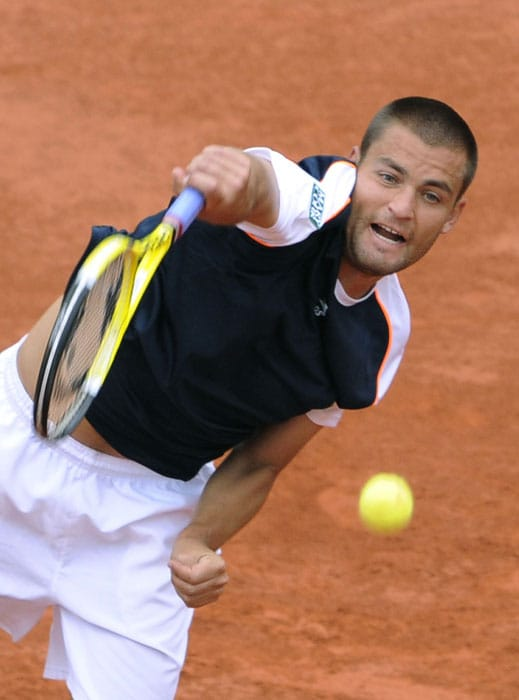 Russia's Mikhail Youzhny returns the ball to France's Jo-Wilfried Tsonga during their men's fourth round match.Tsonga forfeited the match. (AFP PHOTO)