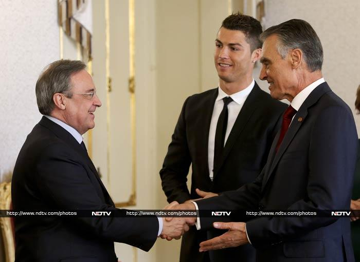Real Madrid's president Florentino Perez (L) is greeted by Silva as Ronaldo watched on.