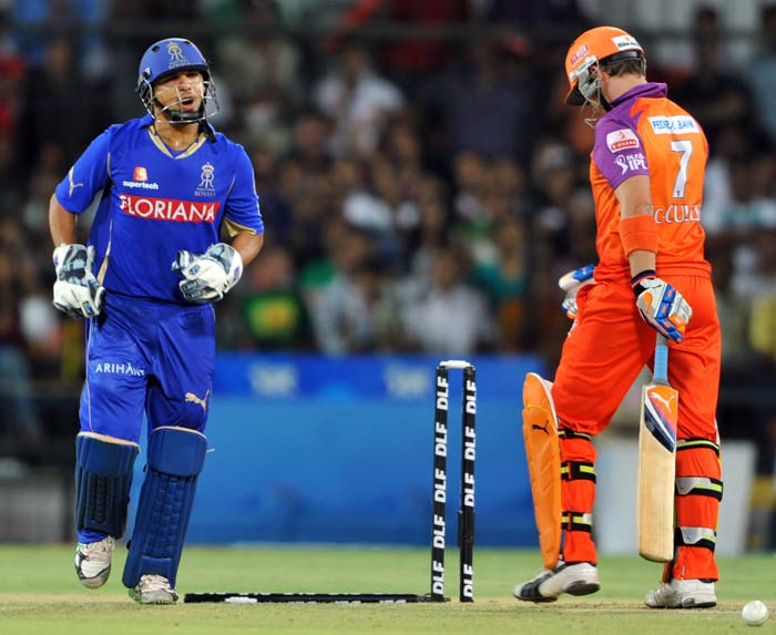 Kochi Tuskers Kerala batsman Brendon McCullum (R) walks back towards the pavilion after being bowled out as Rajasthan Royals wicketkeeper Pinal Shah celebrates during the IPL Twenty20 match at the Holkar Stadium in Indore. (AFP PHOTO)