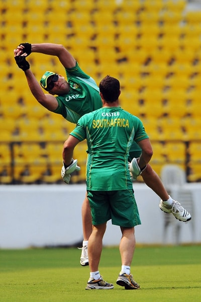Jacques Kallis jumps to collect a ball as wicketkeeper Mark Boucher looks on during a practice session in Nagpur. (AFP Photo)