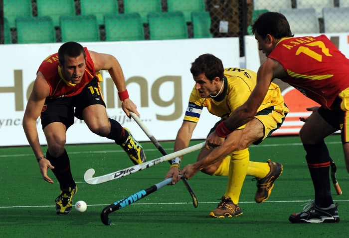 Spanish hockey players Roc Oliva and Albert Sala stops South African hockey player Austin Smith during their hockey World Cup 2010 match at the Major Dhyan Chand Stadium in New Delhi. (AFP Photo)